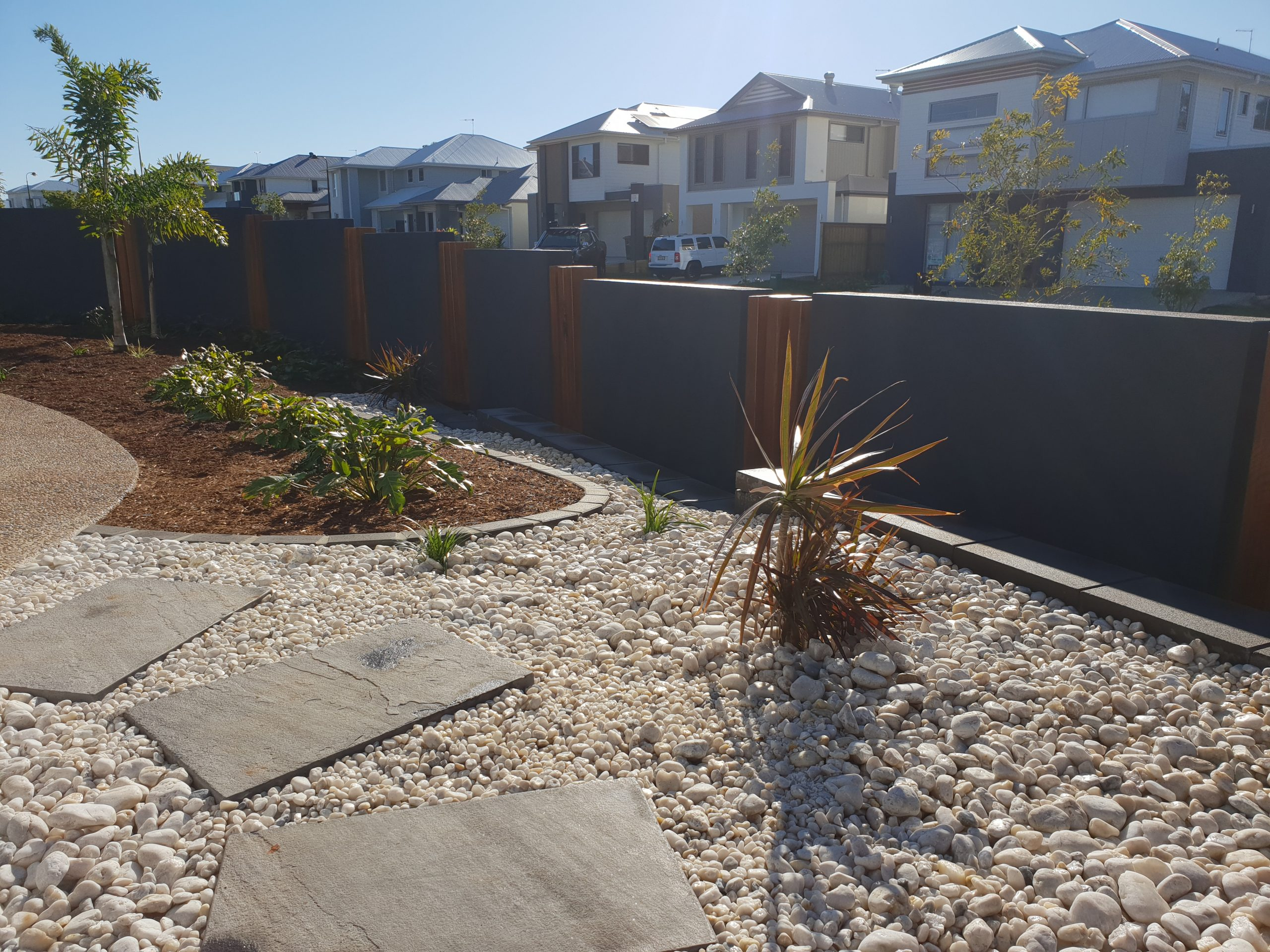 Custom fencing, rock garden with stepping stones, and featured plants