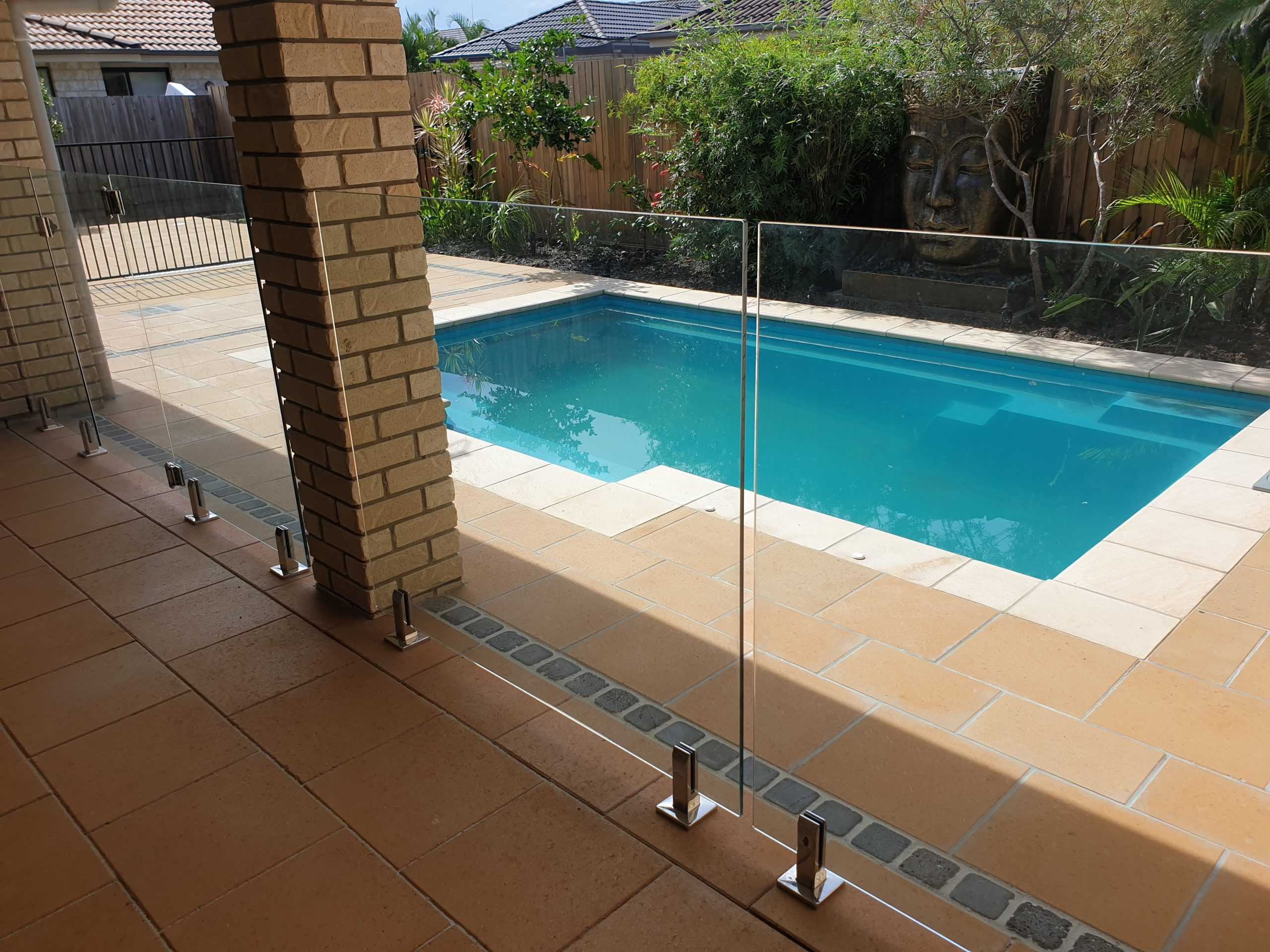 Paving around a swimming pool, with retaining wall and garden