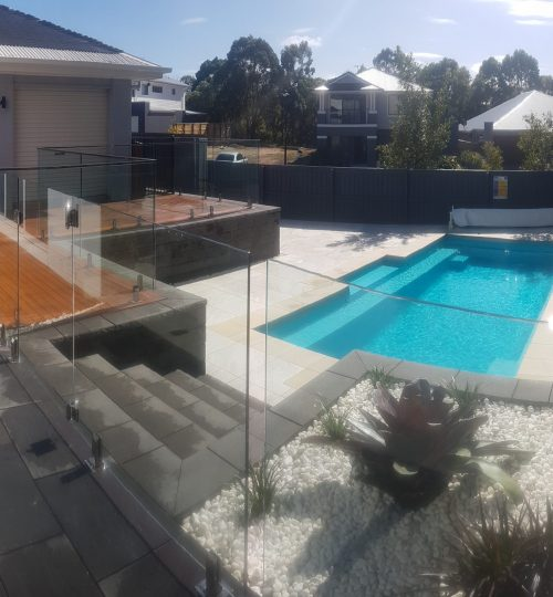 In-ground swimming pool and glass fencing